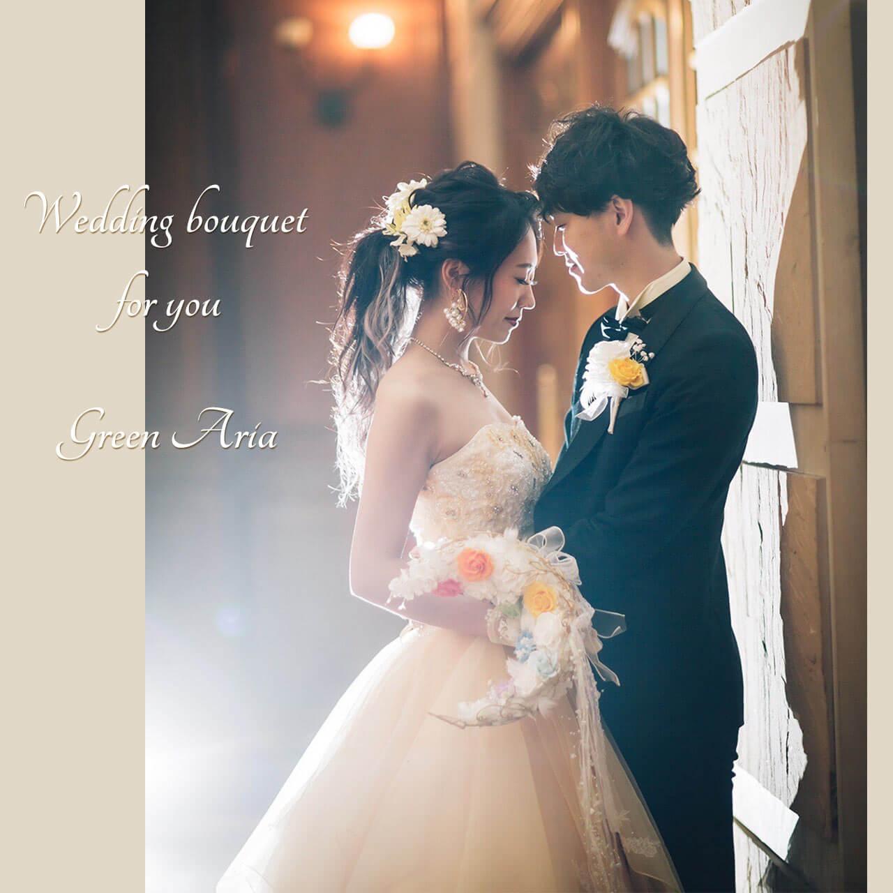 白い三日月に7色の薔薇が入った三日月形ブーケを持ったウエディングドレスの新婦と白とイエローのブートニアをつけた新郎が教会の光の中で向かい合う。